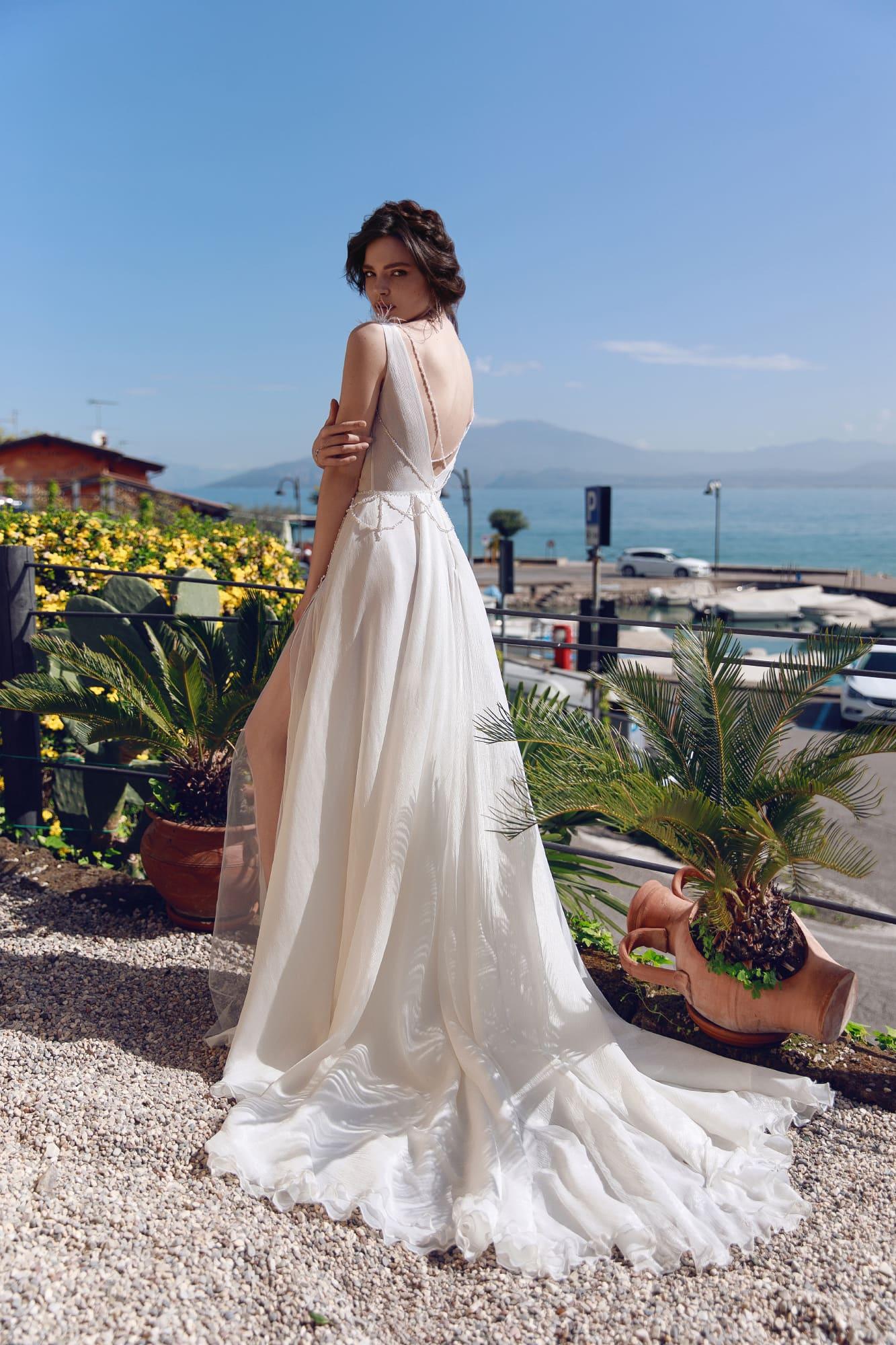 Свадебное платье с отделкой перьями и многослойной юбкой.