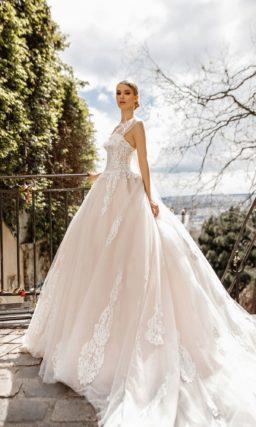 Кремовое свадебное платье с открытым лифом и воздушным шлейфом.