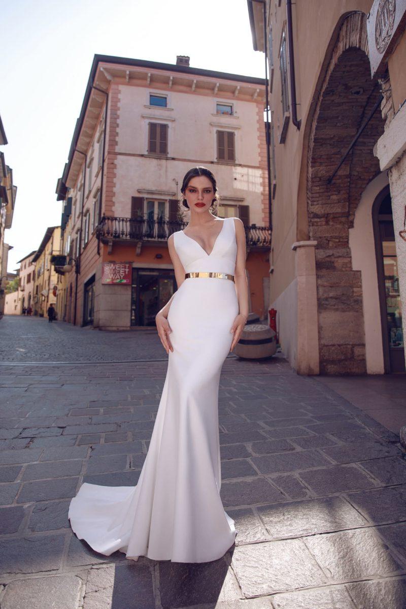 Свадебное платье «русалка» с золотистым поясом и глубоким вырезом.
