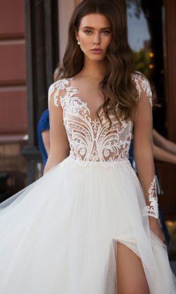 Свадебное платье с разрезом по многослойной юбке и длинным рукавом.