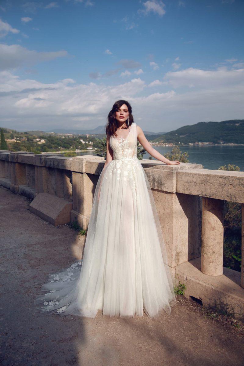 Пышное свадебное платье с полупрозрачным верхом и кружевом.
