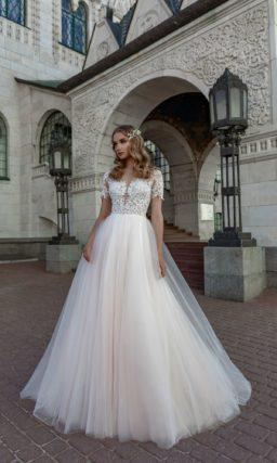 Свадебное платье с кружевным верхом и кремовой юбкой.
