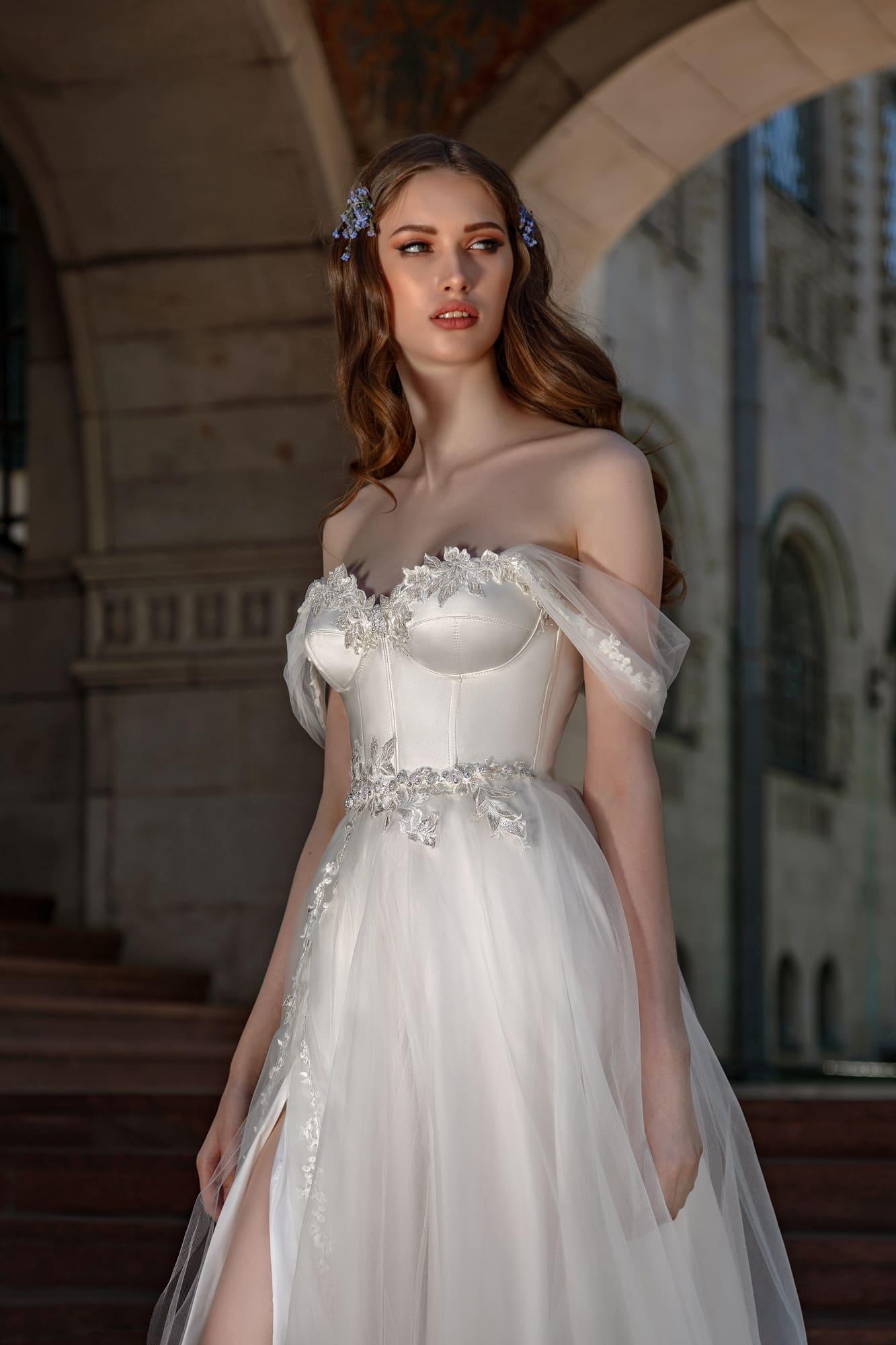 Свадебное платье с открытым верхом и высоким разрезом на юбке.