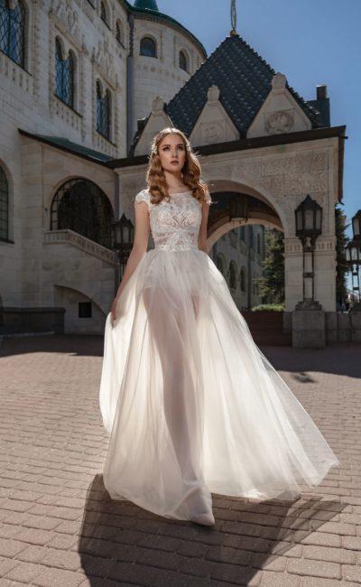 Воздушное свадебное платье с закрытым лифом и полупрозрачной юбкой.