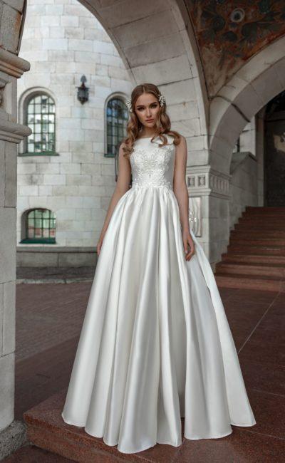 Пышное свадебное платье из атласа, украшенное кружевом по лифу.