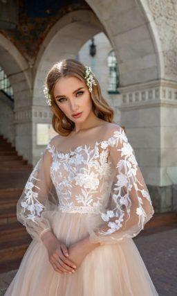 Бежевое свадебное платье с длинным рукавом и белой отделкой.