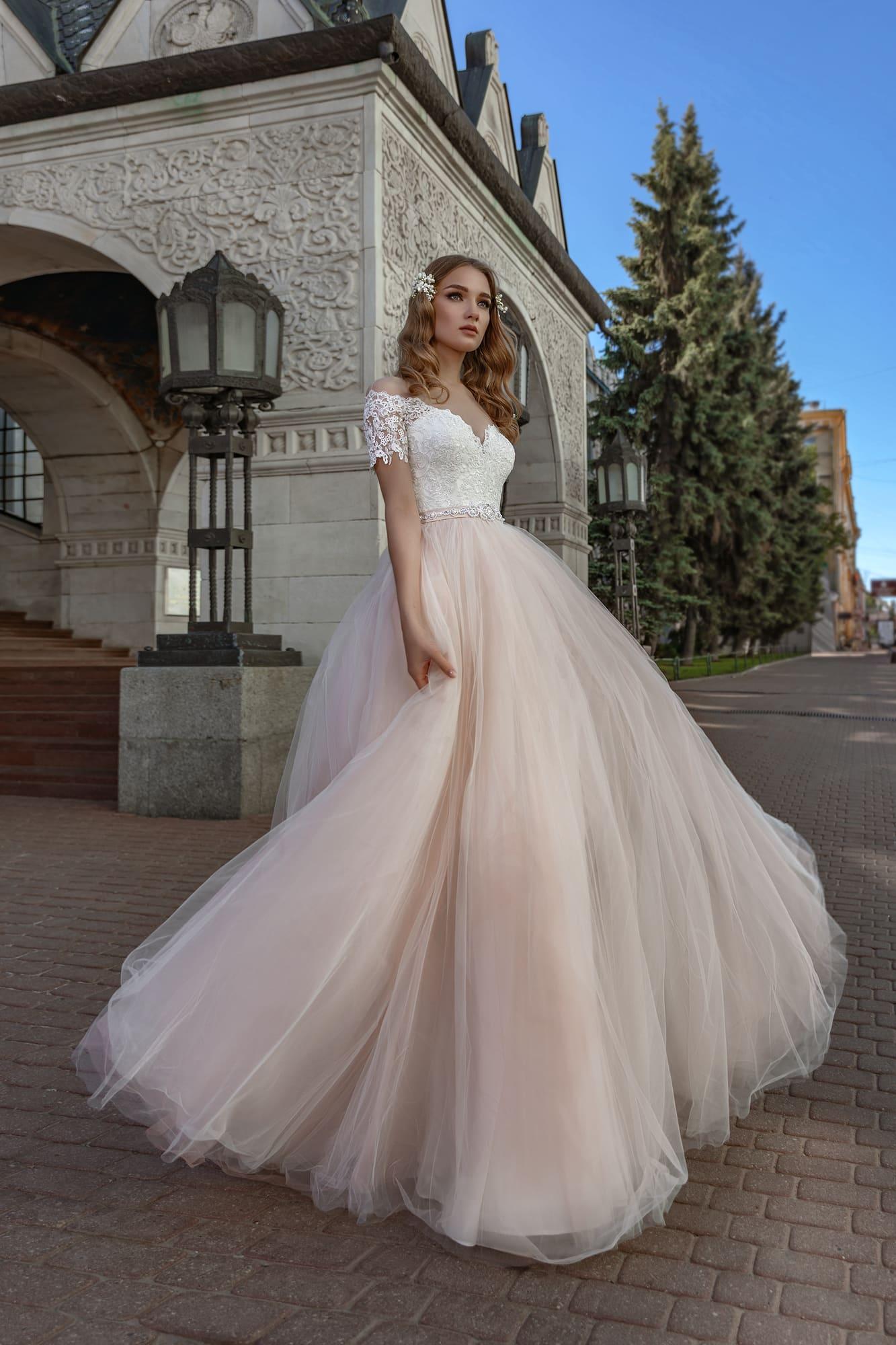 Пышное свадебное платье с портретным декольте и персиковой юбкой.