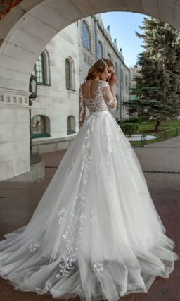 Свадебное платье пышного кроя с прозрачным рукавом и кружевом.