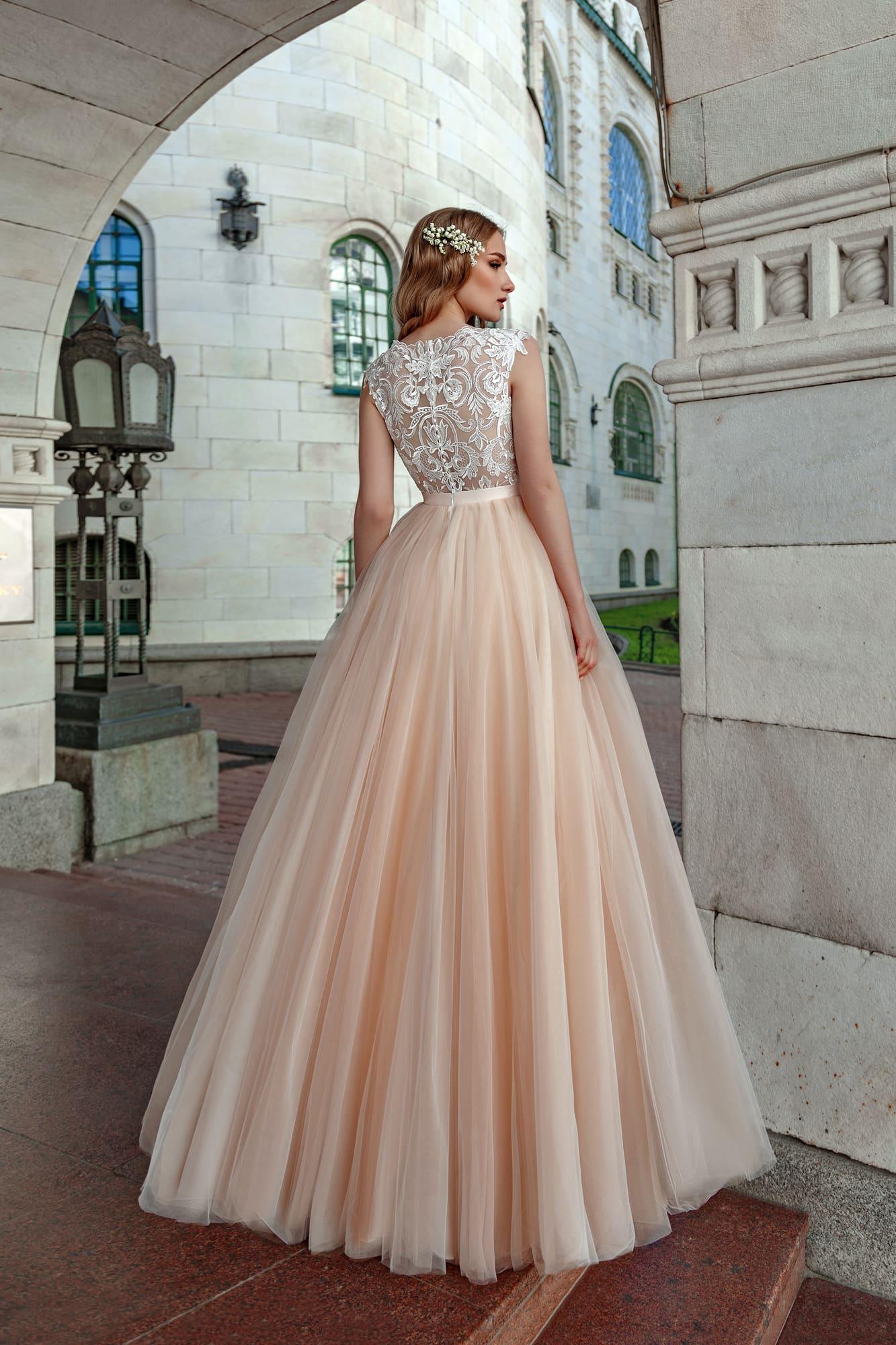 Свадебное платье с полупрозрачным верхом и пышной персиковой юбкой.