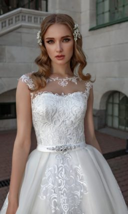 Свадебное платье с кружевным декором и юбкой сложного кроя.