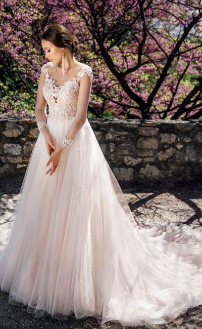 Пышное свадебное платье бежевого цвета с длинным тонким рукавом.