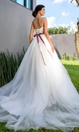 Открытое свадебное платье с алым поясом с объемным бутоном.