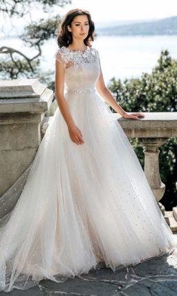 Пышное свадебное платье с кружевным верхом и сияющим поясом.