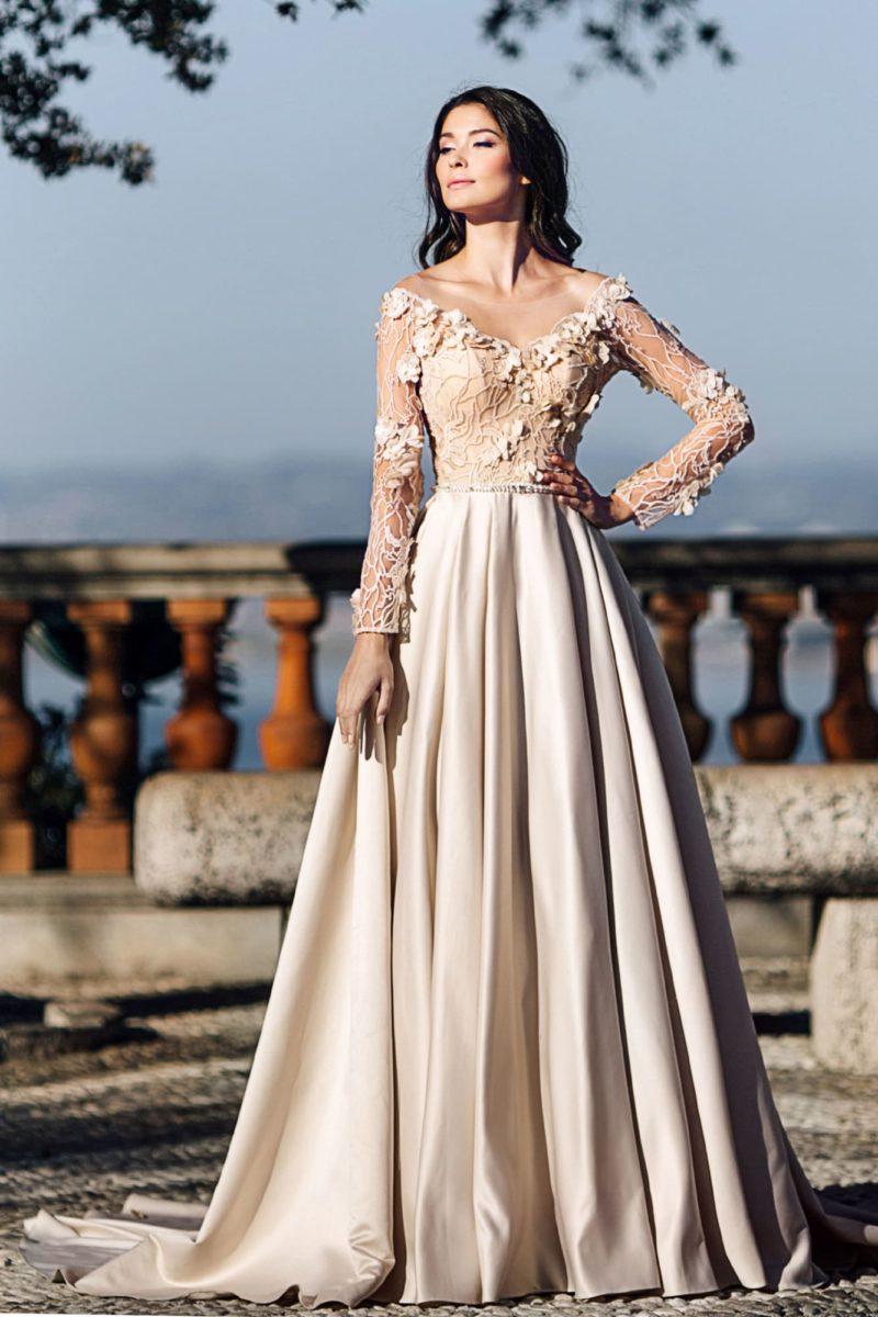 Свадебное платье оттенка айвори с длинным рукавом и юбкой из атласа.